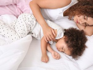 Little African-American girl with mother sleeping in bed